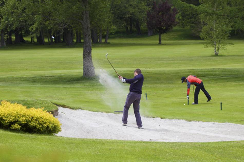 A golfer takes a shot out of a bunker.