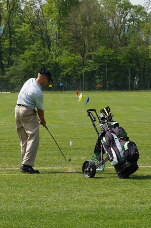 A golfer takes a swing with a hybrid at the driving range.