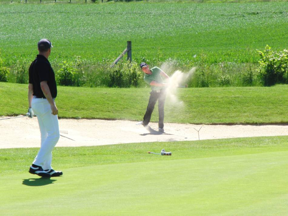 A golfer takes a swing with his sand wedge out of a bunker.