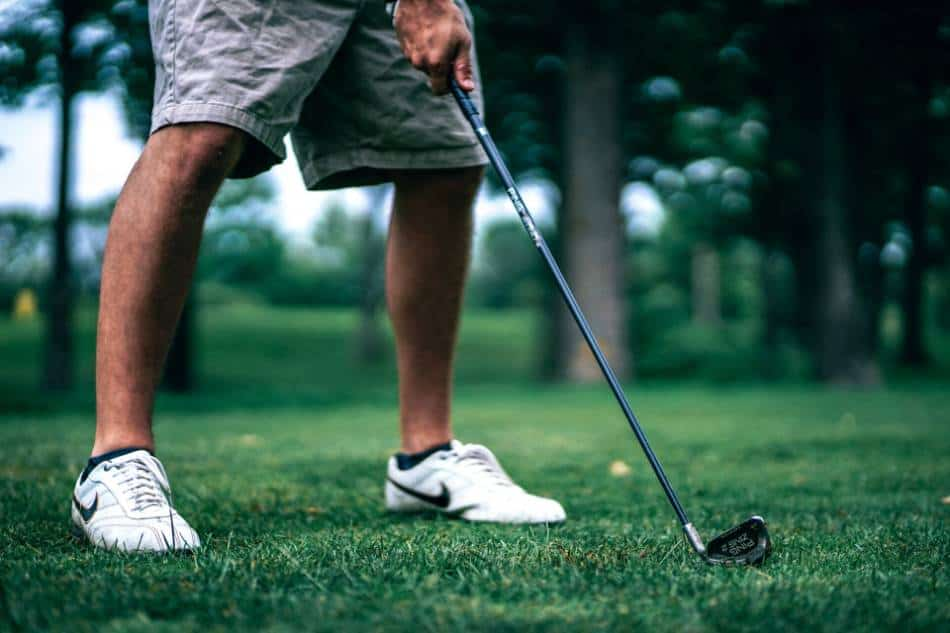 A golfer lines up his iron for a shot.