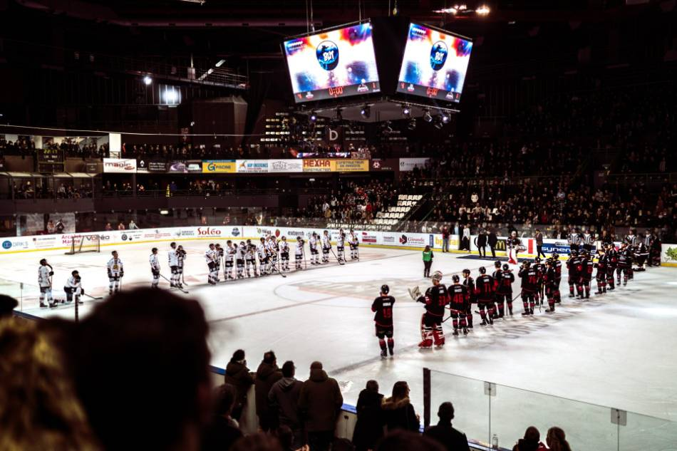 Two professional hockey teams line up at the blue lines for the national anthem(s).