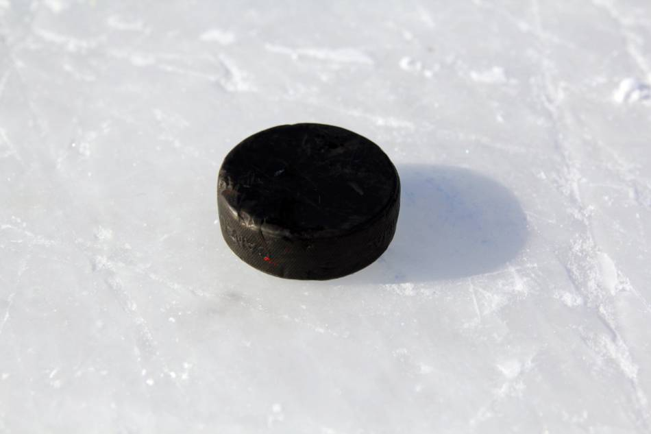 A hockey puck lying on some outdoor ice.