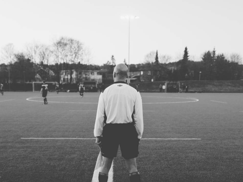 A black and white photo of a soccer linesman watching the game.