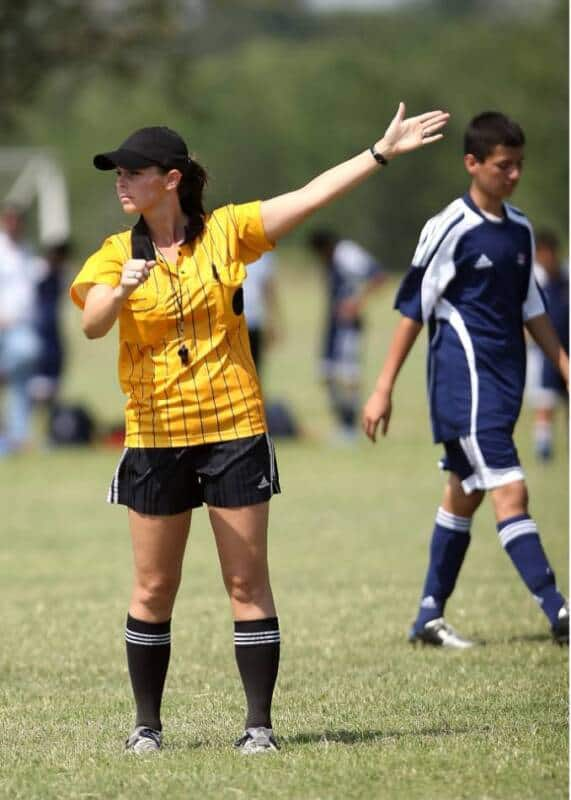 A soccer referee in yellow signal who receives the ball.