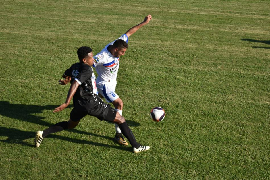 Two soccer players battling for the ball.
